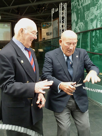 With assistance and 'moral support' from Murray Walker OBE, Sir Stirling Moss, is seen here having cut the ribbon to open the new 'Chequered History' display section at the National Motor Museum, Beaulieu.