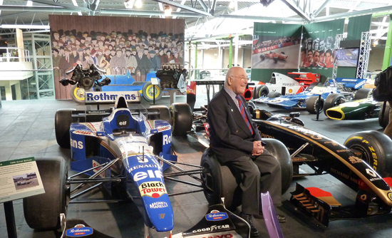 Still absolutely passionate (and deeply knowledgeable) about motor sport, Murray Walker OBE is shown here sat on a front wheel of the 1996 Williams-Renault FW18 car that forms part of the 'Grand Prix Greats' collection at the National Motor Museum.