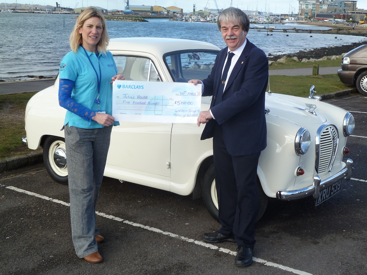 Jacqui Greenhaf, Community Fundraising Manager for Julia's House children's hospice, receives a donation of £500 from the Western Group of Motoring Writers.